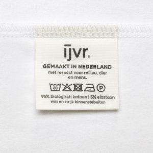 Wit waslabel met wasinstructies van het ijvr T-shirt met de tekst 'Gemaakt in Nederland met respect voor milieu, dier en mens'.